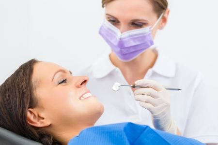 Female patient with dentist in a dental treatment, wearing masks and gloves photo
