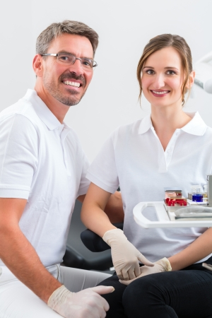 dentists office: Successful Dentists in their surgery looking at the viewer standing side by side Stock Photo