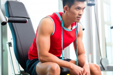 man working out: Asian Chinese man having fitness training or workout in gym doing sport to build up muscle on a weight machine