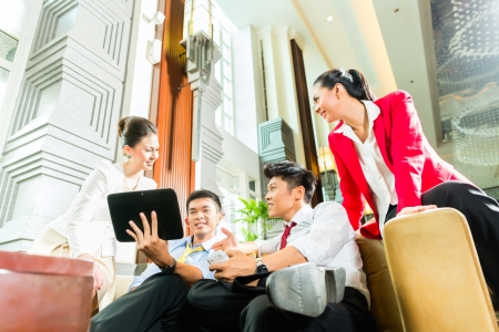 foyer: Group of four Asian Chinese businesspeople meeting for small team discussion in luxurious hotel lobby, there are documents on a tablet computer