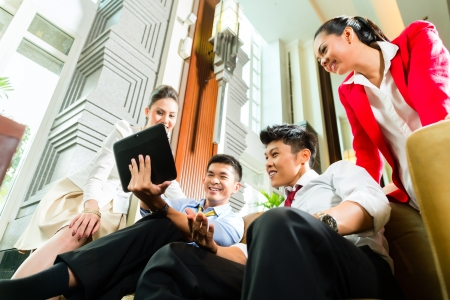 venture: Group of four Asian Chinese businesspeople meeting for small team discussion in luxurious hotel lobby, there are documents on a tablet computer