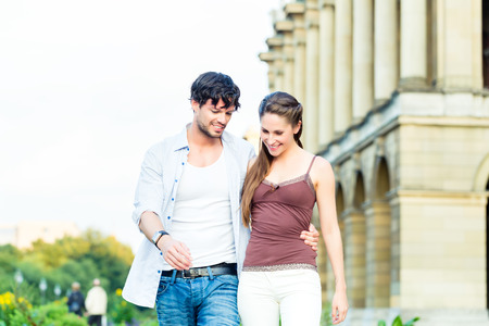 Man and woman or young couple making a trip as tourists in park in front of palace with columns photo