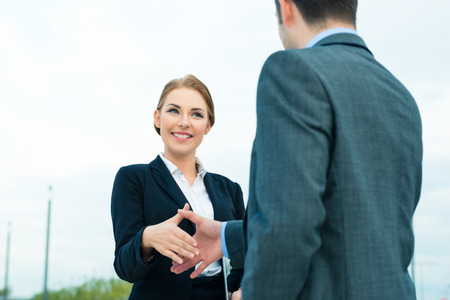 conclude: Business handshake - two businesspeople shaking hands to conclude deal or agreement