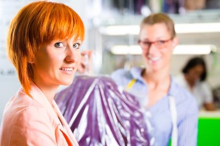 Klant verzamelen kleren in wasserij winkel of textiel stomerij verpakt in tas met hanger Stockfoto