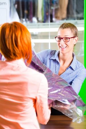 mujer limpiando: Cliente recogida de ropa en la tienda de ropa o textiles de limpieza en seco empacado en bolsa con percha