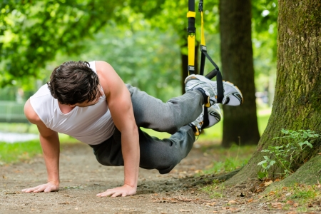 trees  summer: Hombre joven que ejercita con la suspensi�n entrenador honda en parque de la ciudad bajo los �rboles de verano para la aptitud del deporte