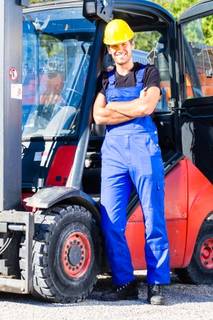 truck driver: builder or driver with pallet transporter or lift fork truck on construction or building site
