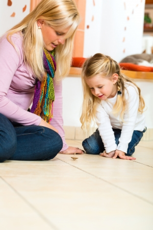 spinner: Girl sitting with mother on floor playing with wooden toy spinner