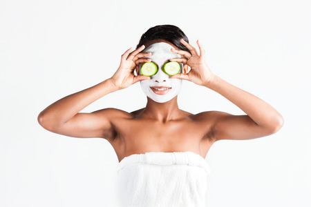 cucumber: Young African woman in Studio doing body care with refreshing cucumber facial mask for young and beautiful skin and relaxation Stock Photo