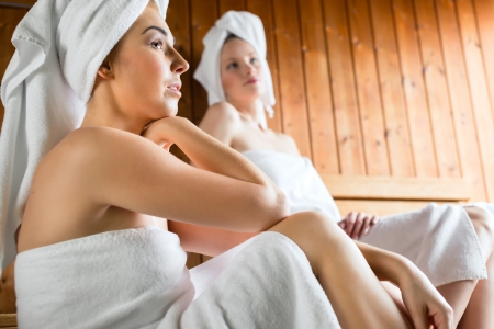 Two Women in wellness spa relaxing in wooden sauna Stock Photo - 25489478