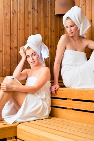 finnish: Two Women in sauna of wellness spa relaxing , enjoying an infusion  Stock Photo