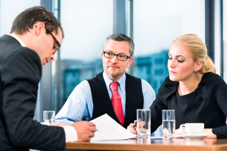 applicant: Business - young man in an Job interview, signs his employment contract with boss and his female assistant in their office