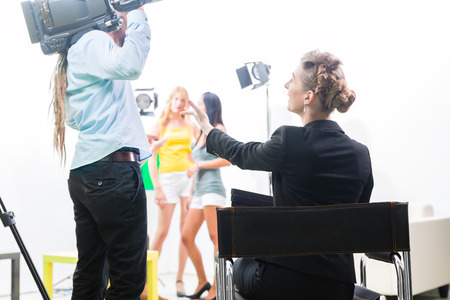 Director giving cameraman shoot or scene direction on set of a video production for TV, television or News  Stock Photo