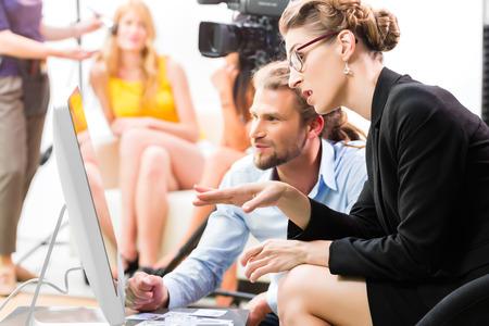 Team of de directeur bespreken tijdens een pauze het toneel richting op de set van een commerciële video productie of reportage op een scherm