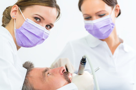 dentist in her practice or office treating male patient with assistant wearing masks and gloves