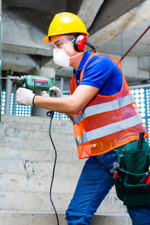 walling: Asian Indonesian builder or construction site worker worker drilling with a machine or drill, ear protection, mask and  hardhat or helmet  in a wall of a tower building