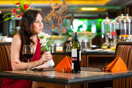 Chinese nervous, hoping, lonely, dreamy, heartsick woman in a restaurant waiting for a date got stood up  Stock Photo - 25602567
