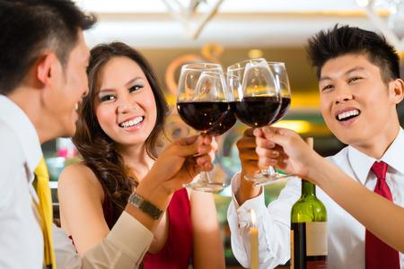 food on table: Due coppie o amici o uomini d'affari tostatura durante la cena o il pranzo in un ristorante elegante con bicchieri di vino rosso cinese asiatici