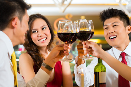 Two Asian Chinese Couples or friends or business people toasting during dinner or lunch in a elegant restaurant with red wine glasses Stock Photo - 25602570