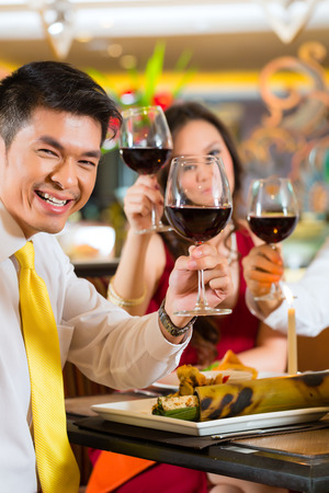 business dinner: Two Asian Chinese Couples or friends or business people toasting during dinner or lunch in a elegant restaurant with red wine glasses