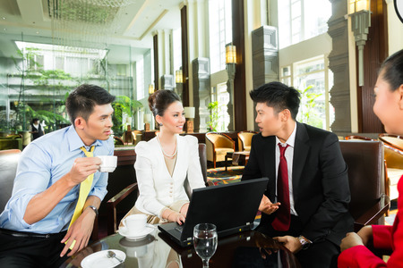 asian business: Four Asian Chinese office people or businessmen and businesswomen having a business meeting in a hotel lobby discussing documents on a tablet computer while drinking coffee