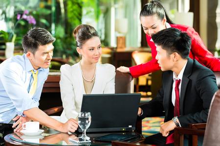 business: 討論文件平板電腦上一邊喝咖啡四個亞洲中國辦公室的人或商人和其在酒店大堂的商務會議商人