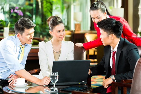 coffee meeting: Four Asian Chinese office people or businessmen and businesswomen having a business meeting in a hotel lobby discussing documents on a tablet computer while drinking coffee