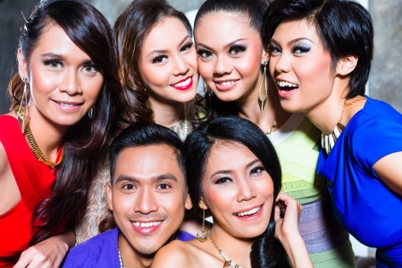 group picture: Asian young and handsome group of party people or friends taking pictures in fancy night club Stock Photo