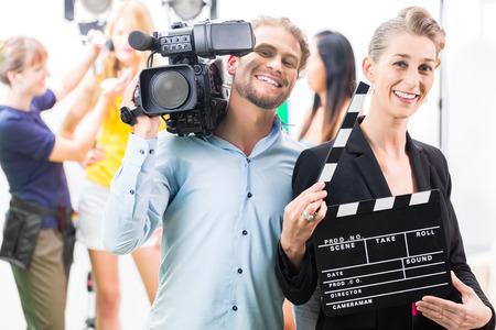 hombre disparando: Equipo o Cameraman con la cámara y la mujer con la toma aplaudir o tablero en Rodajes Foto de archivo