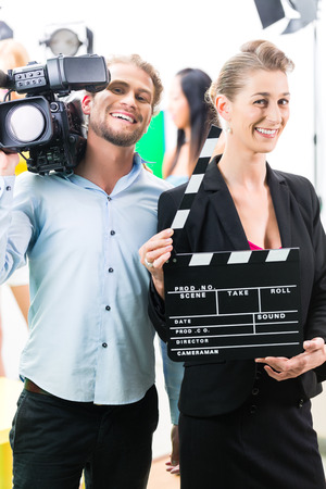 film shooting: Team or Cameraman with camera and woman with take clap or board on Film Set