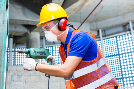 Asian Indonesian builder or construction site worker worker drilling with a machine or drill, ear protection, mask and  hardhat or helmet  in a wall of a tower building  photo