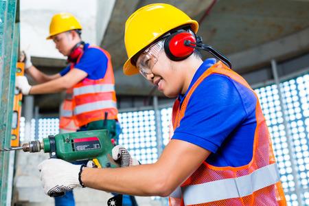 Aziatische Indonesische bouwplaatsmedewerkers boren met een of boormachine, waterpas, gehoorbescherming, handschoenen en helm of helm in een muur van een toren bouwen Stockfoto