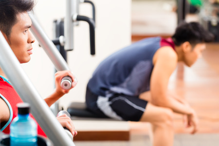 build up: Chinese men having fitness training or workout in gym doing sport to build up muscle on a weight machine Stock Photo