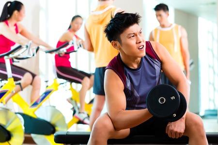 Grupo asiático chino de hombres y mujeres que realizan ejercicio de deporte o entrenamiento en el gimnasio de fitness con pesas con barra para obtener más poder