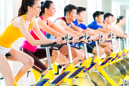 spinning: Chinese Asian sport group of men and women in fitness club or gym exercising on spinning bikes
