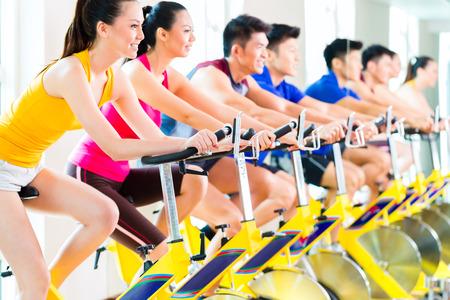 fitness training: Chinese Aziatische sport groep van mannen en vrouwen in fitness club of sportschool te oefenen op spinningfietsen