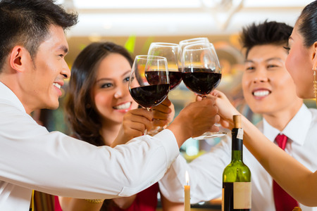 Two Asian Chinese Couples or friends or business people toasting during dinner or lunch in a elegant restaurant with red wine glasses Stock Photo - 25602814
