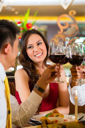 gourmet dinner: Two Asian Chinese Couples or friends or business people toasting during dinner or lunch in a elegant restaurant with red wine glasses
