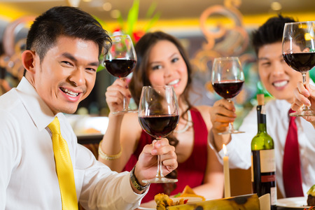 Two Asian Chinese Couples or friends or business people toasting during dinner or lunch in a elegant restaurant with red wine glasses Stock Photo - 25602843