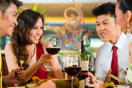 adult dating: Two Asian Chinese Couples or friends or business people toasting during dinner or lunch in a elegant restaurant with red wine glasses