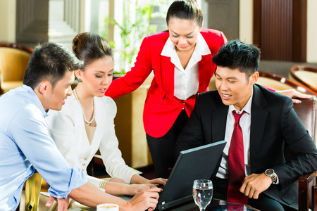 Four Asian Chinese office people or businessmen and businesswomen having a business meeting in a hotel lobby discussing documents on a tablet computer while drinking coffee  photo