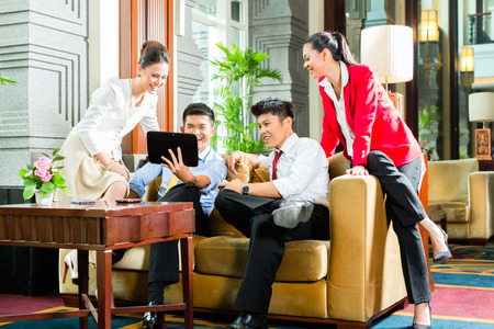 Group of four Asian Chinese businesspeople meeting for small team discussion in luxurious hotel lobby, there are documents on a tablet computer  photo