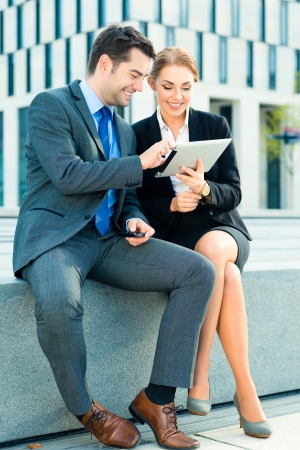 business people or businessman and businesswoman working outdoor, using pad or tablet computer and mobile cell phone photo