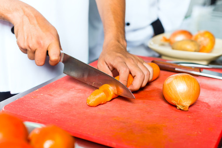 Asian Indonesian chef along with other cooks in restaurant or hotel commercial kitchen cooking, slicing a carrot photo
