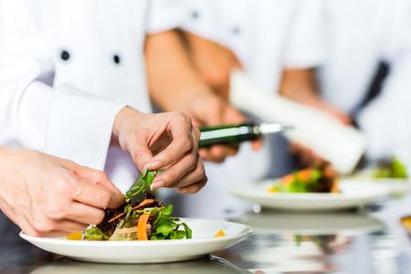 Aziatische Indonesische chef-kok samen met andere koks in restaurant of hotel commerciële keuken koken, afwerken schaal of bord