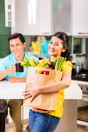Young Asian handsome woman coming home from grocery shopping Stock Photo