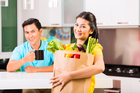 coming home: Young Asian handsome woman coming home from grocery shopping Stock Photo