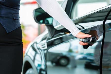 売り手または車のセールスマンと握手、彼らのディーラーの顧客車のキーを引き渡すし、シールの自動または新しい車の購入