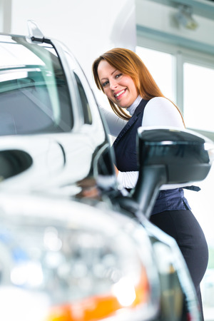 test drive: Young woman beside a new car in car dealership, obviously she is buying the auto, or making a test drive