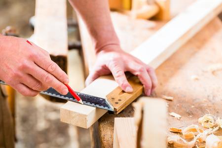Timmerman die aan houten werkstuk in zijn atelier of timmerwerk